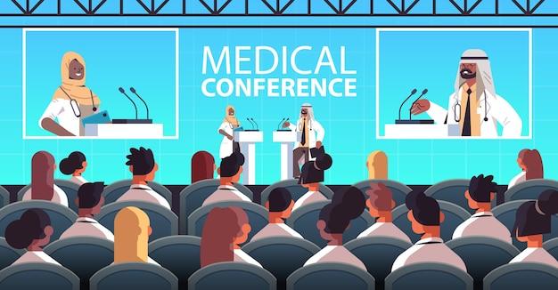 Casal de médicos árabes fazendo discurso na tribuna com microfone conferência médica reunião medicina conceito de saúde sala de aula ilustração vetorial horizontal interior