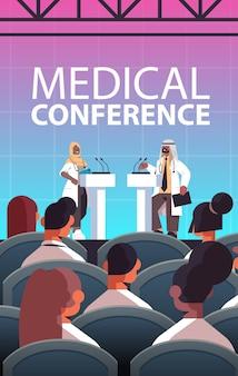 Casal de médicos árabes fazendo discurso na tribuna com microfone conferência médica reunião medicina conceito de saúde sala de aula ilustração vetorial vertical interior