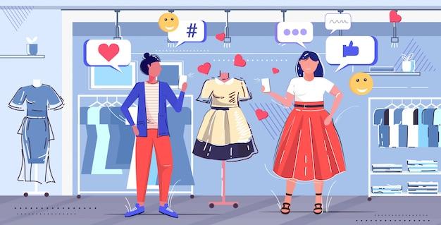 Casal de meninas escolhendo novo vestido mulheres clientes usando o aplicativo móvel on-line redes sociais conceito de moda moderna boutique de moda interior esboço comprimento total horizontal