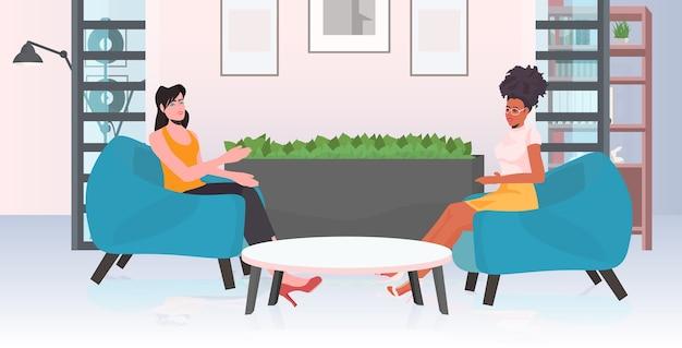 Casal de mulheres de raça mista discutindo durante reunião na área de conferência movimento de empoderamento feminino união de poder feminino do conceito de feministas