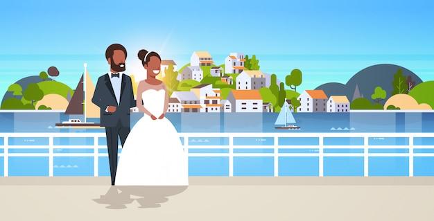 Casal de noivos em pé juntos noiva e noivo abraçando o dia do casamento conceito montanha cidade ilha paisagem fundo horizontal