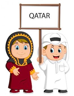 Casal de qatar dos desenhos animados vestindo trajes tradicionais