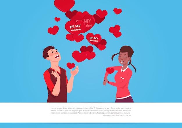 Casal de raça mix sobre coração formas com ser meu valentine cartões conceito de férias dia amor