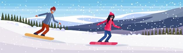 Casal de snowboarder descendo a montanha