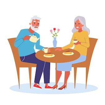 Casal de velhinhos feliz sentado à mesa tomando chá