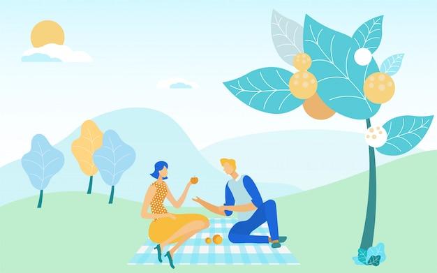 Casal desfrutando refeição de fim de semana, sentado no piquenique.