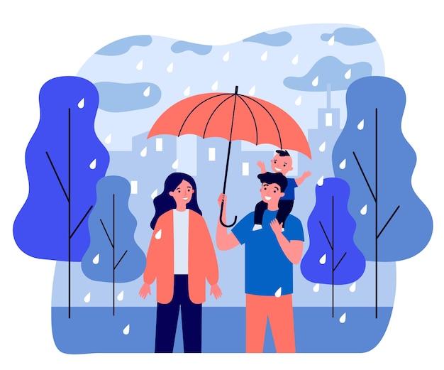 Casal feliz com criança andando em dia chuvoso