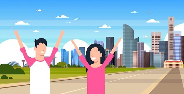 Casal feliz de turistas sobre a paisagem urbana de singapura ver com monumentos e arranha-céus famosos