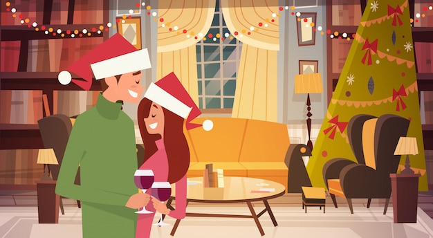 Casal feliz em chapéus de papai noel abraçando na sala de estar decorada para feliz natal e feliz ano novo