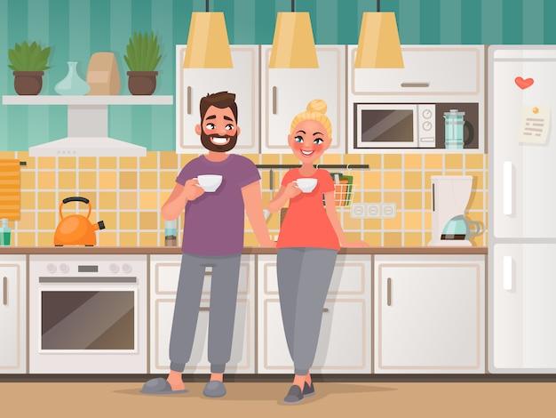 Casal feliz na cozinha. homem e mulher bebem chá em casa