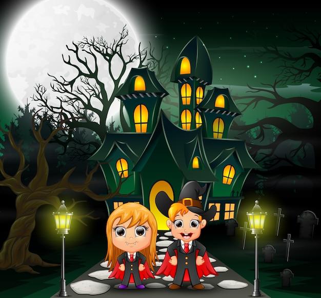 Casal feliz vampiro na frente da casa assombrada