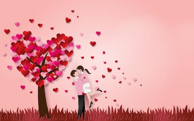 Casal fofo se abraçam no chão de grama com árvore do coração