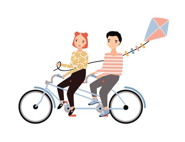 Casal fofo vestido com roupas da moda, andando de bicicleta tandem e segurando pipa