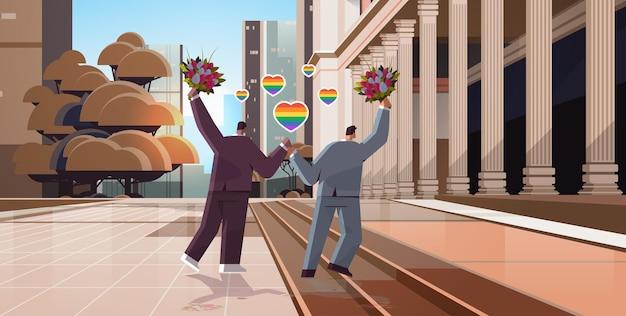 Casal gay recém-casado com flores caminhando ao ar livre transgênero ama a celebração de casamento da comunidade lgbt