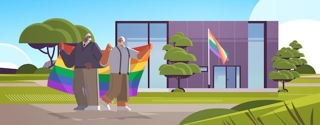 Casal gay sênior segurando a bandeira do arco-íris perto de uma nova casa modular para transexuais que ama o conceito de comunidade lgbt