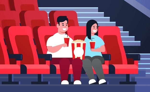 Casal gordo assistindo filme sentado no cinema com pipoca e coca-cola excesso de peso homem mulher tendo data e rindo de nova comédia