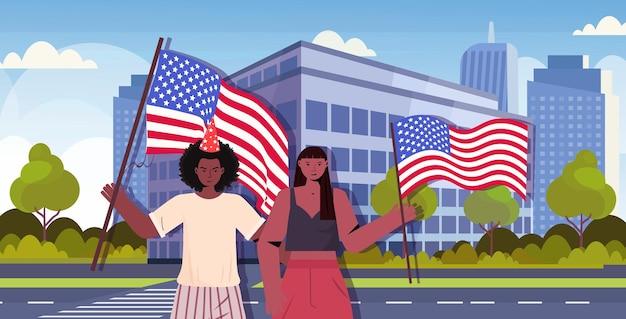 Casal homem mulher segurando bandeiras dos eua comemorando 4 de julho, dia da independência americana