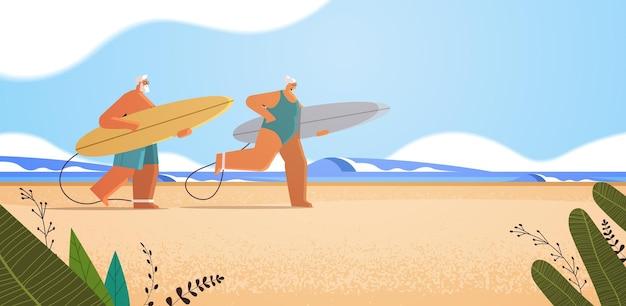 Casal idoso com pranchas de surf envelhecida homem mulher surfistas segurando pranchas de surf conceito de velhice ativa das férias de verão