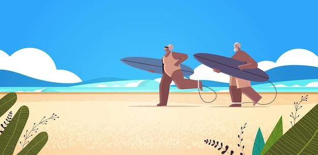 Casal idoso com pranchas de surf, homem, mulher, surfistas, segurando pranchas de surf, férias de verão, velhice ativa