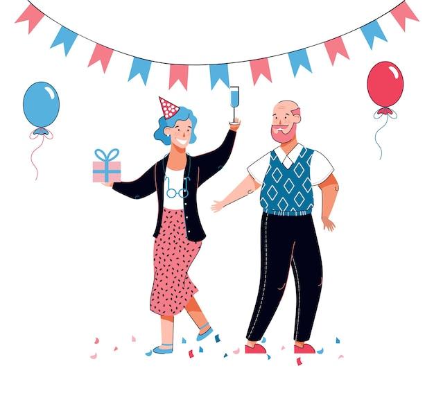 Casal idoso na festa de aniversário com chapéu de festa, balões e caixa de presente