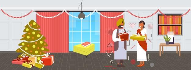 Casal indiano dando caixas de presentes um ao outro feliz natal férias de inverno conceito de celebração moderna sala de estar