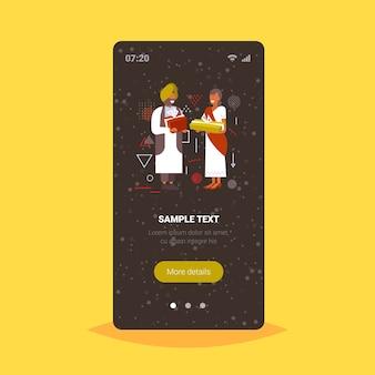 Casal indiano dando caixas de presentes um ao outro feliz natal, férias de inverno, conceito de celebração tela do smartphone aplicativo móvel on-line ilustração vetorial de corpo inteiro