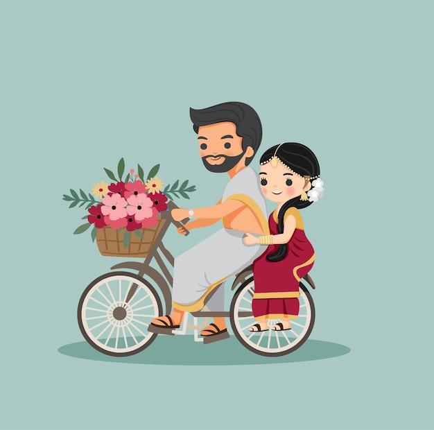 Casal indiano fofo com bicicleta com flor em vestido tradicional