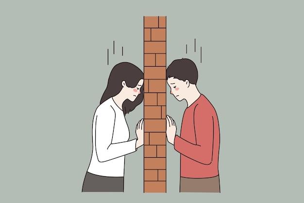 Casal infeliz em luta separado por uma parede de tijolos
