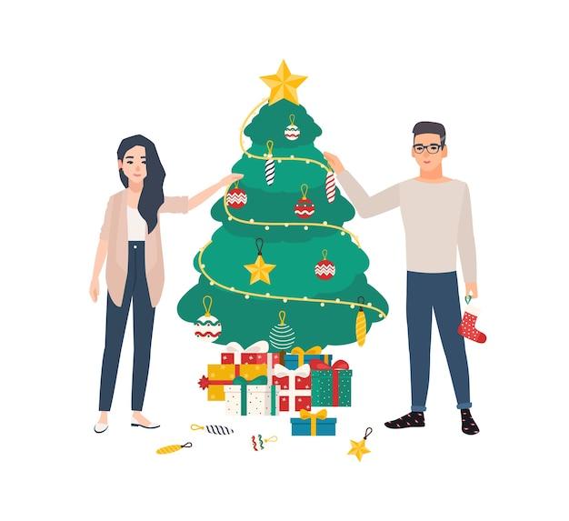 Casal jovem bonito decorando a árvore de natal com enfeites e guirlandas leves.