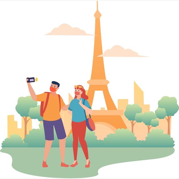 Casal mascarado de turistas tirando fotos em frente à torre eiffel durante um novo feriado normal