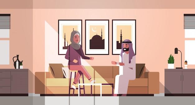 Casal muçulmano comemorando ramadan kareem mês sagrado sala de estar interior homem árabe mulher em roupas tradicionais, discutindo durante a reunião horizontal comprimento total