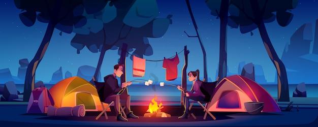 Casal no acampamento com tenda e fogueira à noite