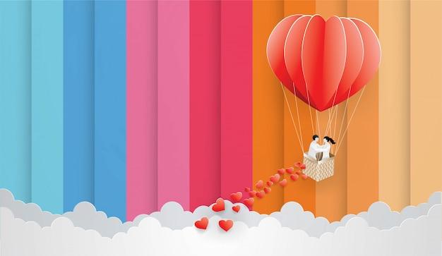 Casal no balão vermelho sobre o fundo do céu de cor.
