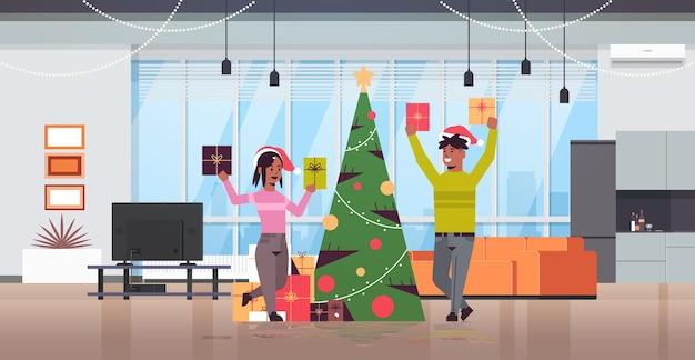Casal segurando caixas de presente embrulhado feliz natal feliz ano novo feriado celebração conceito homem mulher vestindo chapéus de papai noel moderna sala de estar interior plana comprimento total horizontal vetor ilustr
