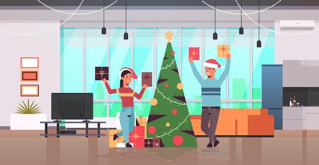 Casal segurando caixas de presentes embrulhadas feliz natal feliz ano novo feriado celebração conceito homem mulher vestindo chapéus de papai noel moderna sala de estar interior plana comprimento total horizontal vetor