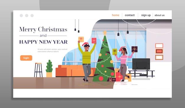 Casal segurando caixas de presentes feliz natal feliz ano novo feriado celebração conceito homem mulher vestindo chapéus de papai noel sala de estar moderna página de destino interior