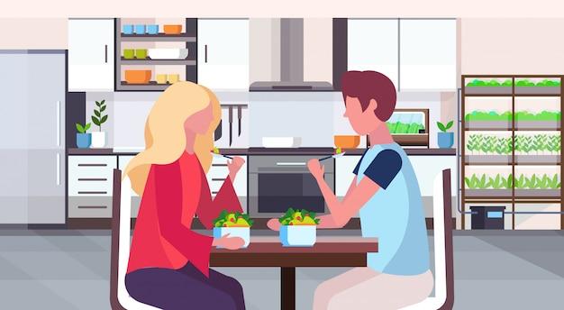 Casal sentado na mesa homem mulher comendo salada de frutas frescas conceito de comida saudável sala moderna com plantas inteligentes crescendo sistema cozinha interior retrato horizontal plana