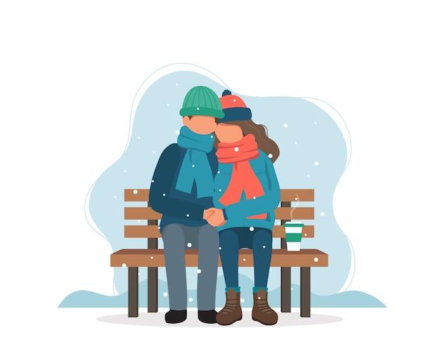 Casal sentado no banco no inverno com café.
