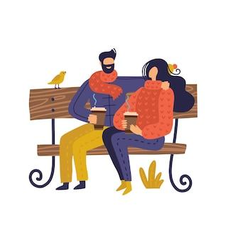 Casal sentado no banco no outono com café.