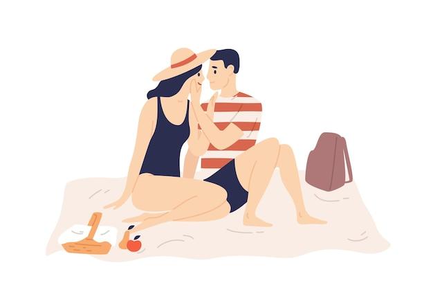 Casal sorridente em traje de banho senta-se na manta e tem um encontro romântico ao ar livre.