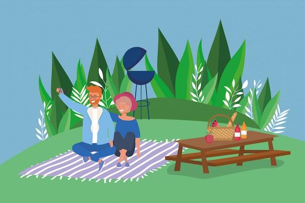 Casal tomando selfie cobertor mesa comida cesta grelha árvores piquenique