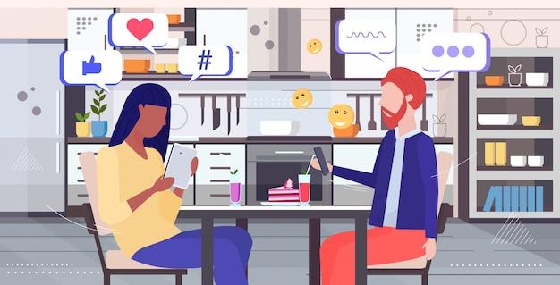 Casal usando o aplicativo móvel on-line rede social bate-papo bolha conceito de comunicação conceito mistura raça homem mulher sentada na mesa cozinha moderna interior retrato retrato horizontal