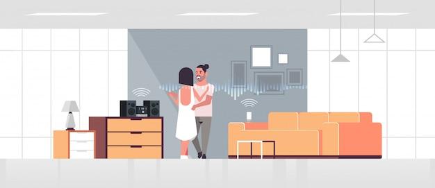 Casal usando o sistema de som hi-fi controlado por alto-falante inteligente