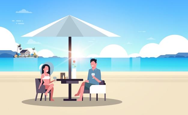 Casal verão férias homem mulher bebida vinho guarda-chuva no nascer do sol praia villa casa ilha tropical