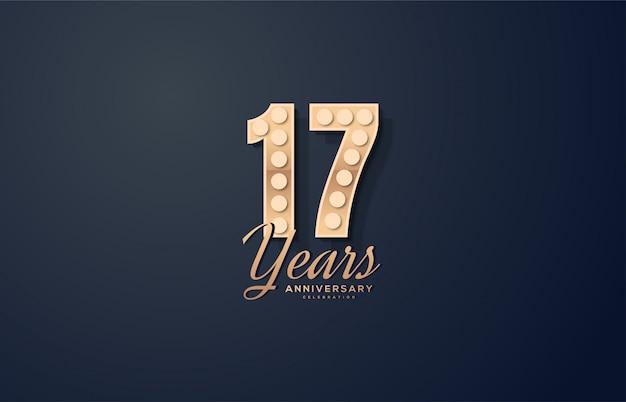 Celebração do 17º aniversário com números rodeados por luzes douradas.