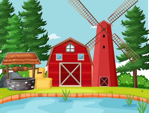 Celeiro vermelho e moinho de vento no cenário da natureza