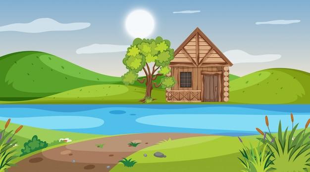 Cena com chalé de madeira no campo junto ao rio