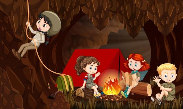 Cena com crianças felizes, acampar na caverna à noite