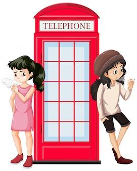 Cena com dois adolescentes fumando na cabine telefônica
