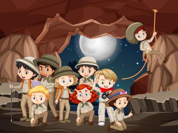 Cena com muitas crianças na caverna à noite